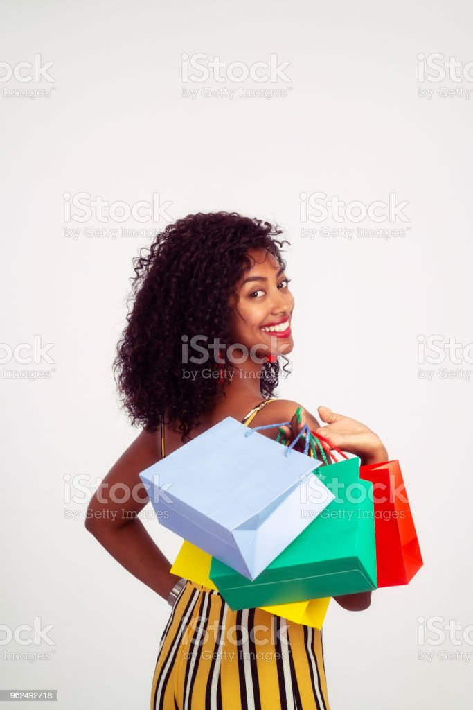 Shopping is my passion! Portrait of beautiful young woman with curly hair. The woman holding colored shopping paper bags. - Royalty-free 20-29 Years Stock Photo