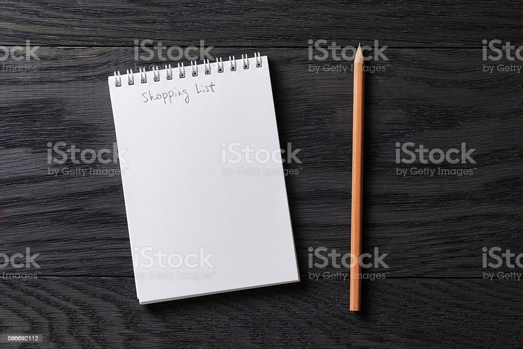 shopping list phrase in notepad on gray wood table stock photo