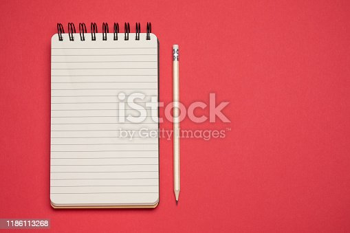 Spiral notebook and pencil on red background