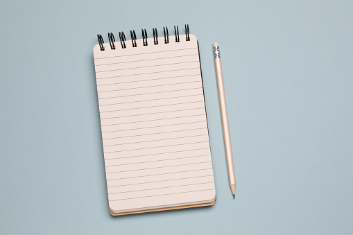 Spiral notebook and pencil on blue background