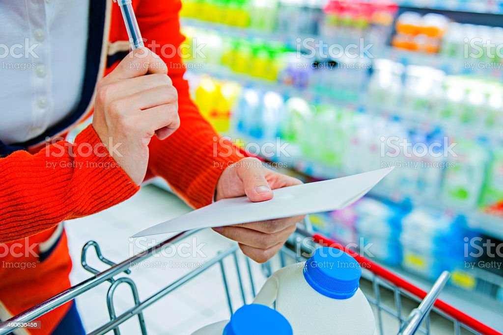woman hand holding shopping list in a supermarket.