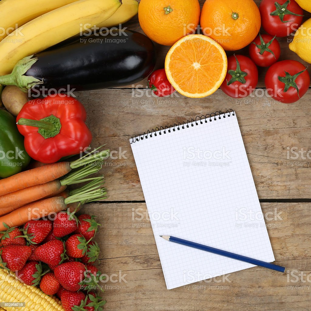 Shopping list with fruits and vegetables on a wooden board stock photo