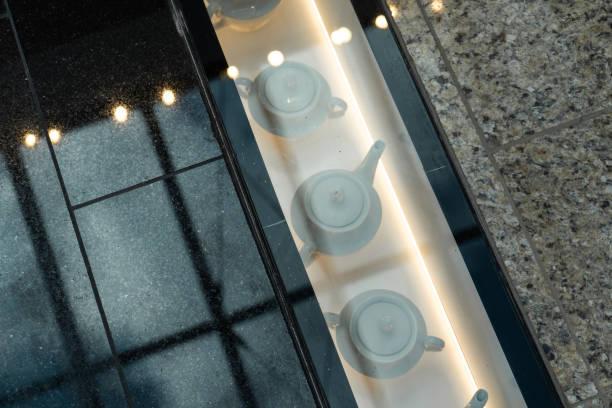 einkaufszentren dekoration-teekannen unter einem glasboden - museum für naturkunde stock-fotos und bilder