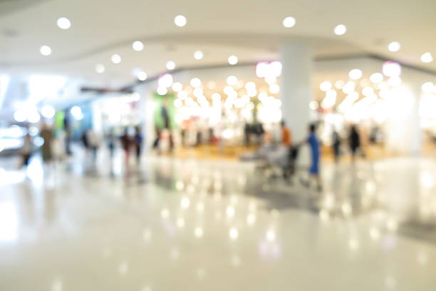 shopping mall, modern trade with people in blur background - shopping mall stock photos and pictures