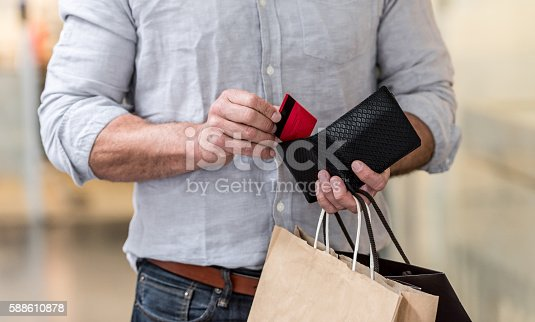 Unrecognizable shopping man putting credit card in his wallet while walking at the mall. Design on card is own design.