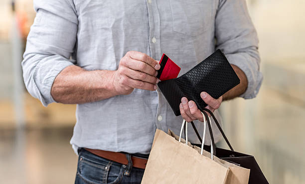 shopping man putting credit card in his wallet - geld uitgeven stockfoto's en -beelden