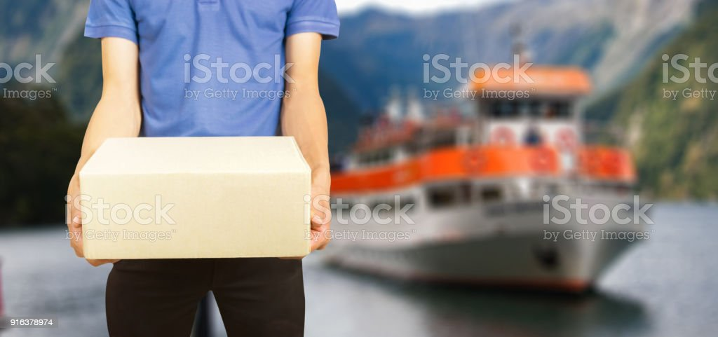 shopping online  and order concept,male postal delivery courier   package to home over General cargo ship mooring at port wait cargo handling from industrial factory riverside stock photo