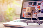 istock Shopping online concept - Parcel or Paper cartons with a shopping cart logo in a trolley on a laptop keyboard. Shopping service on The online web. offers home delivery. 1249219777