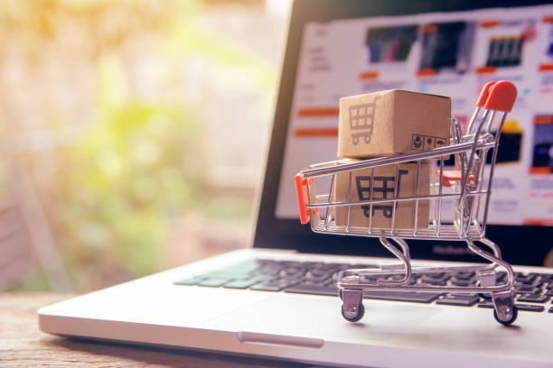 conceito on-line de compras - caixas de papel ou parcelas com um logotipo de carrinho de compras em um carrinho em um teclado portátil. serviço de compras na internet. oferece entrega domiciliar. - mercadoria - fotografias e filmes do acervo