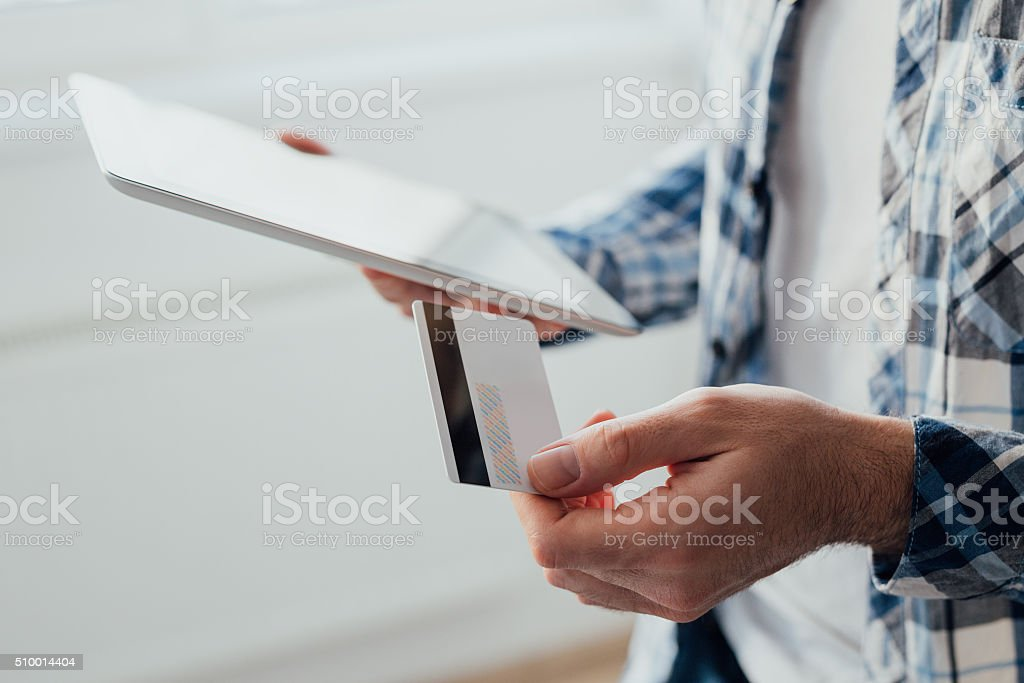 Shopping online concept Young man using tablet while holding credit card. Shopping online concept Adult Stock Photo