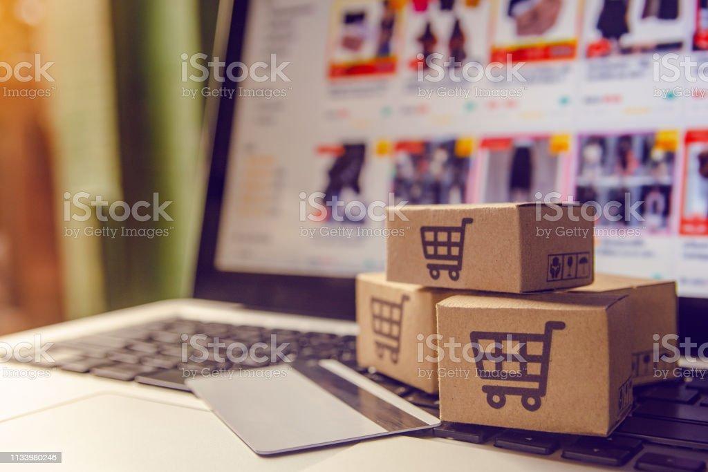 Shopping Online concept-shopping service op het online web. met betaling per creditcard en biedt levering aan huis. pakje of papieren kartons met een winkelwagentje logo op een laptop toetsenbord - Royalty-free Bedrijfsleven Stockfoto