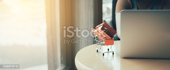 Shopping online concept with woman using laptop in cafe.
