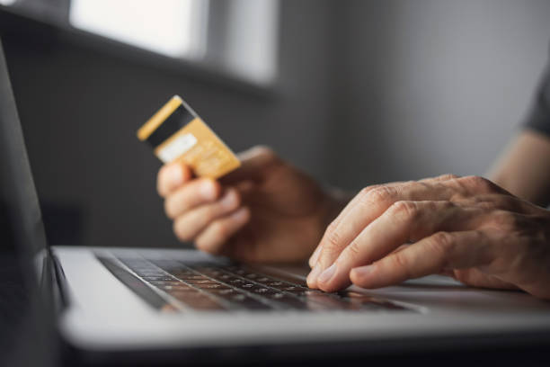Shopping online. Young man using laptop with credit card at home stock photo