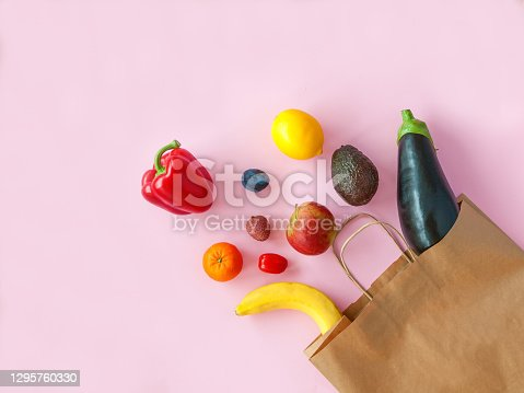 Shopping paper bag with different fruits and vegetables on a pink background, flat lay.