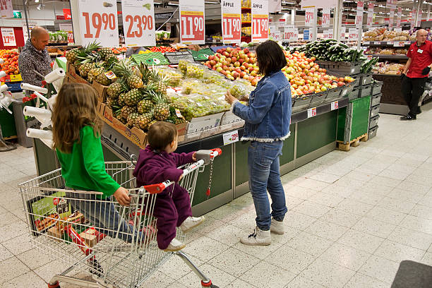 Shopping Åkersberga, Sweden - October, 01th 2011:A woman and children near fruit stand. The Willys market place is in Åkersberga, Sweden. willys stock pictures, royalty-free photos & images