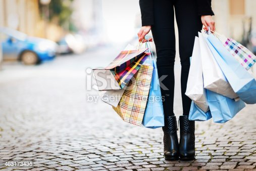 Woman legs and shopping bags holding in hands.