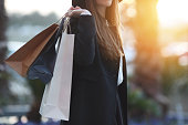 Shot of a woman using her phone while shopping in a boutiqueYoung woman shopping in the city, legs and hands close up, carrying paper bags.Young woman shopping in the city, legs and hands close up, carrying paper bags.