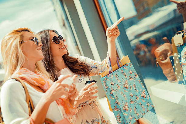 Shopping Happy woman with shopping bags pointing finger in the shop window. boutique stock pictures, royalty-free photos & images