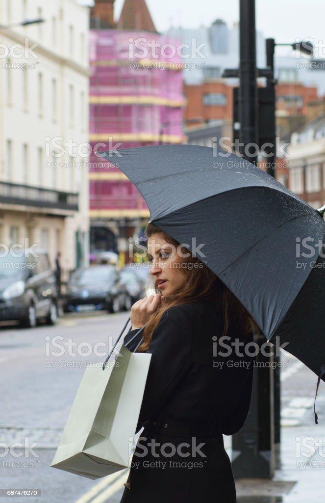 Shopping Russian outdoor girl umbrella in rainy Belgravia stock photo