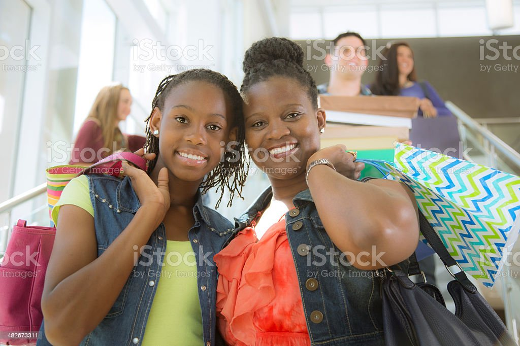 Shopping spree!  Mother, daughter hold many bags in mall. stock photo