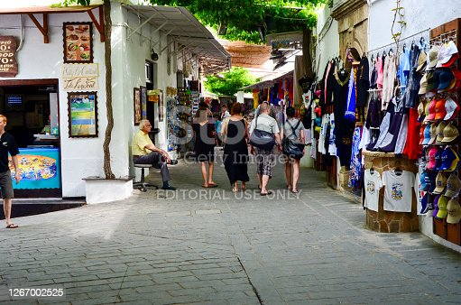 Lindos, Greece, May 22, 2012 - Shopping street in the old town of Lindos, Rhodes with some unidentified people in the background.