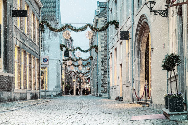 winkelstraat met kerstverlichting en sneeuwval in de nederlandse stad van maastricht - maastricht stockfoto's en -beelden