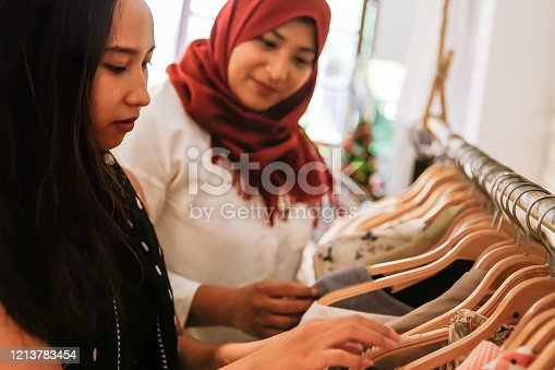 Close up two females Asian friends going shopping vintage clothes together in a thrift market