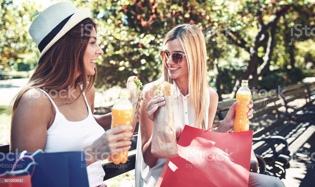 Shopping time. Beautiful women resting in the park after shopping. Consumerism, shopping, lifestyle concept stock photo