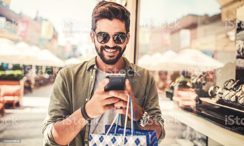 Shopping time. Modern young man with shopping bags making a phone call. Consumerism, shopping, lifestyle concept stock photo