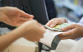Grocery store clerk handing change back to customer at checkout, selective focus