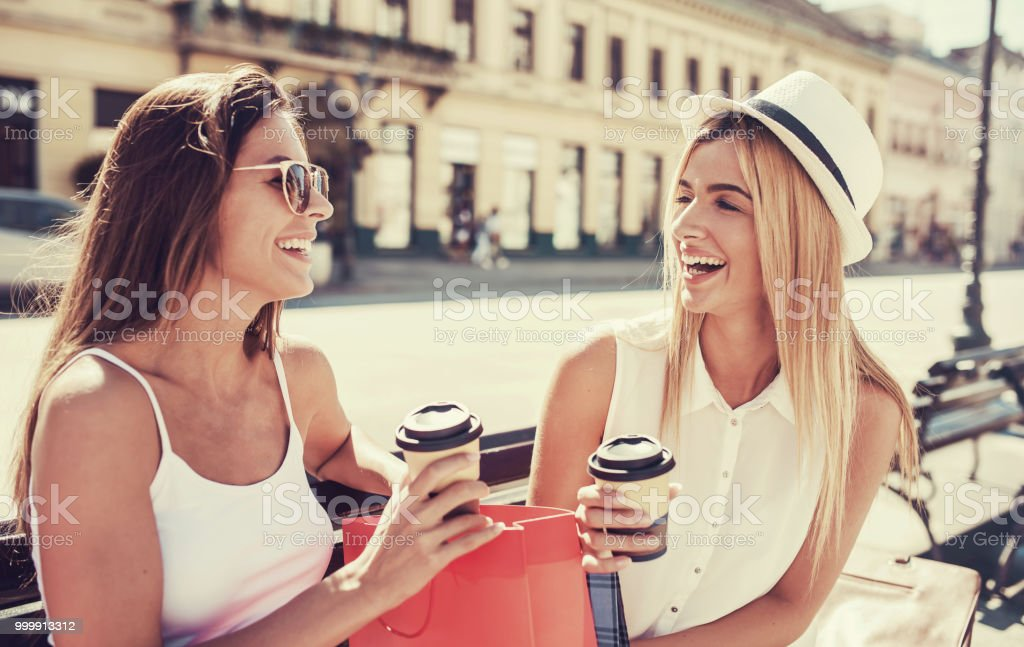 Women in shopping. Two beautiful women sitting on the bench after...
