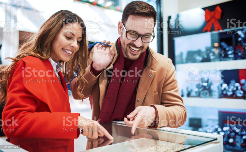 Shopping time. Young couple looking at jewels in jewelry shop. Consumerism, love, dating, lifestyle concept stock photo