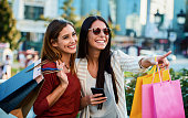 Women in shopping. Two happy women with shopping bags enjoying in shopping, having fun in the city. Consumerism, fashion, lifestyle concept