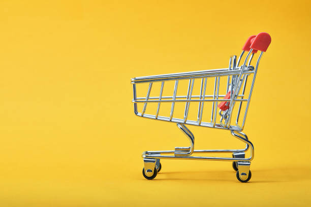 shopping trolley on yellow background with some copy space stock photo