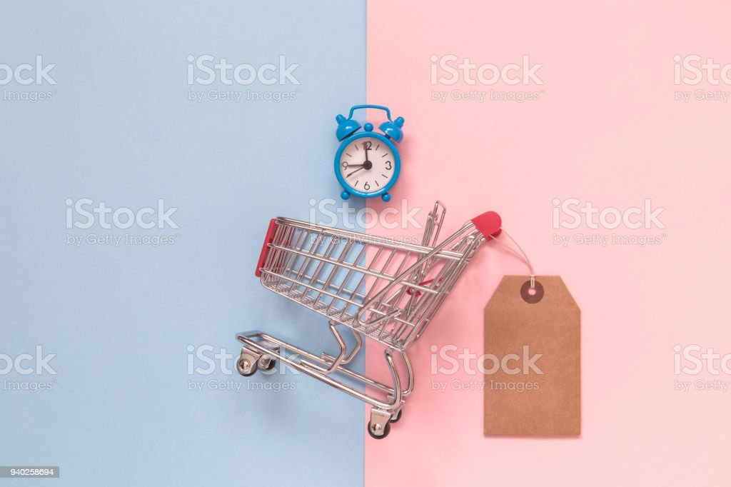 Shopping trolley toy with special offer tag and blue alarm clock on pastel background minimalistic flat lay concept. stock photo