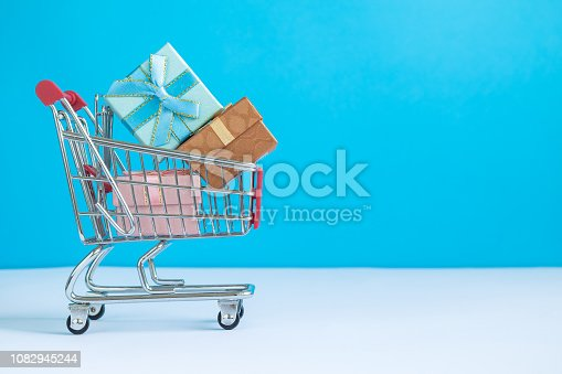 1136804881 istock photo Shopping trolley with christmas presents abstract. Space for copy. 1082945244