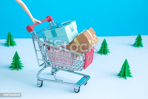1136804881 istock photo Shopping trolley with colorful gift boxes and origami christmas trees in the background. 1082946552