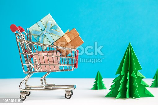 1136804881 istock photo Shopping trolley with presents and origami christmas trees abstract. Space for copy. 1082954182