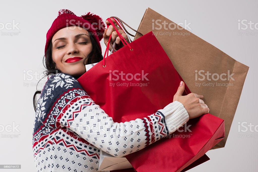 Shopping winter woman embracing shopping bags stock photo