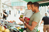 Father holding his son while they are out shopping, looking at different fruits.