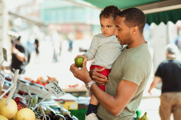 Shopping with a Healthy Lifestyle Father holding his son while they are out shopping, looking at different fruits. farmer's market stock pictures, royalty-free photos & images