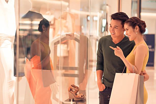 Shopping with husband Young woman showing something in the shop window to her husband shopping couple asian stock pictures, royalty-free photos & images