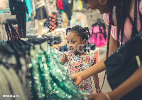 4 year old cute little girl and her mother, with long braids, are shopping in a store together, looking at a sparkly skirt, smiling, happy and cute. A day to day happy moment of childhood and parenting and shopping for new clothes, mother daughter bonding