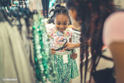 4 year old cute little girl and her mother, with long braids, are shopping in a store together, looking at a sparkly skirt, smiling, happy and cute. Mother holds up skirt to daughter to see if it will fit. A day to day happy moment of childhood and parenting and shopping for new clothes, mother daughter bonding