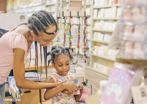 Woman and Child, little girl, 4 years old, African American mother and daughter, browse a shop, candid, happy, light and bright, they are enjoying time and shopping together