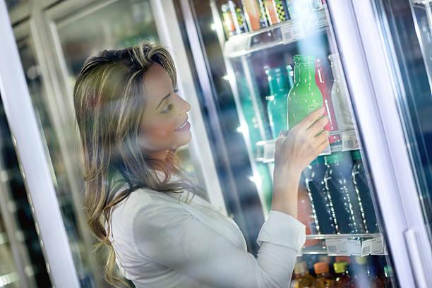 shopping woman buying a drink at the supermarket - teeladen stock-fotos und bilder