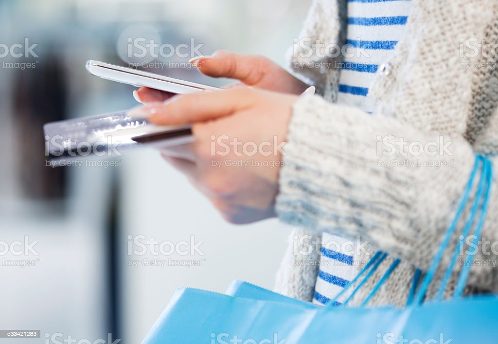 Shopping woman holding a Smartphone and Credit card stock photo