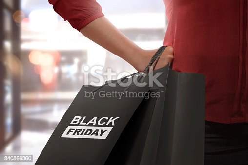 istock Shopping woman holding Black Friday paper bags 840866360