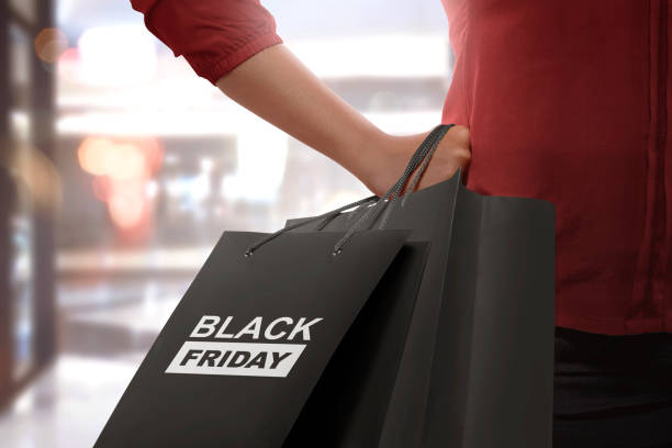 Shopping woman holding Black Friday paper bags stock photo