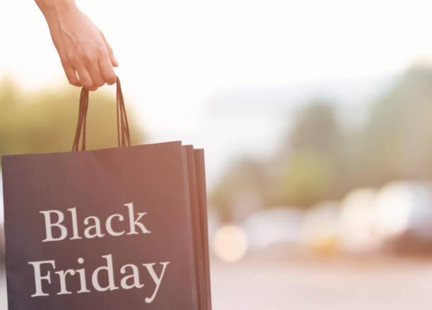shopping femme tenant des sacs en papier coloré - black friday photos et images de collection